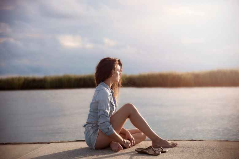 woman in blue denim jacket sitting near body of water